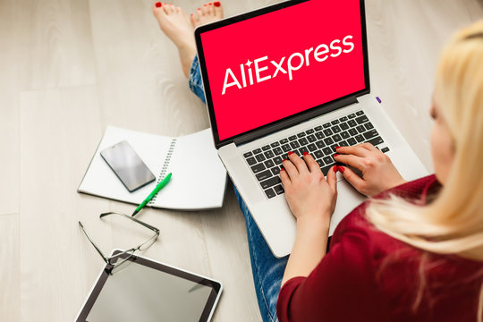 Kyiv, Ukraine - November 10, 2019: Woman holding macbook pro with Internet shopping service Aliexpress on the screen.