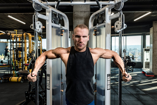 Young strong sweaty focused fit muscular bodybuilder man chest stretching workout on cable machine in the gym  for strength and good looking of muscles training