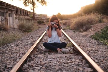 Chica joven viajera sentada en las vías del tren haciendo fotos con cámara analógica al atardecer