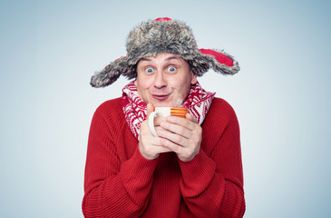 Funny happy man in a red sweater, scarf and winter hat holds a mug of hot drink in his hands