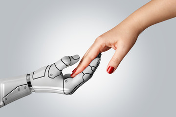 Robotic cyborg hand holding female human hand on gray background. People and artificial intelligence technology concept.