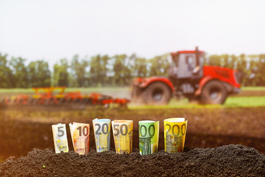 Euro Money. Different Euro banknotes from 5 to 200 Euro on Agriculture Tractor plowing field background.
