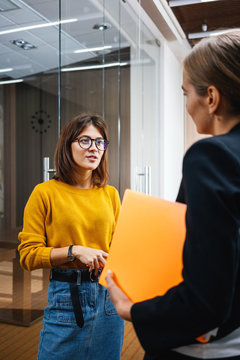 Two young positive businesswoman meeting in openspace office. Female coworker conversation indoor contemporary business center