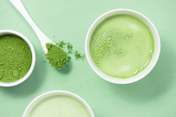 Cup of matcha tea with milk on the green table and matcha powder