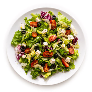 Fresh greek salad on a plate on white background
