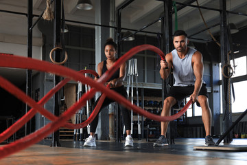 Papiers peints Fitness Athletic young couple with battle rope doing exercise in functional training fitness gym.