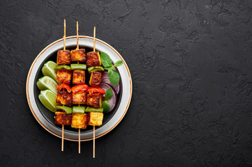 Paneer Tikka at skewers in black bowl at dark slate background. Paneer tikka is an indian cuisine dish with grilled paneer cheese with vegetables and spices. Indian food. Top view. Copy space