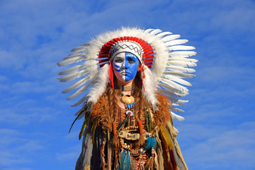 A young girl plays the part of a native American Indian  girl. She wears a white feathered headdress  and has her face painted blue and white.