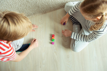 Two clever children study mathematics playing with colorful dices