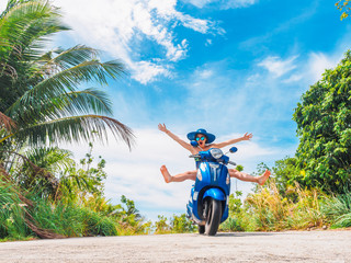 Crazy funny woman with flying hair riding a motorbike on a blue sky and green tropics background....