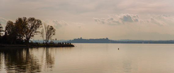 Misty view of Lake Trasimeno in Umbria with Isola Maggiore (Greater Island) and Castiglione del Lago old town and walls in the background