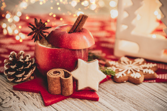 christmas baked apple for christmas in christmas decoration with cinnamon stick and orange and advent candle