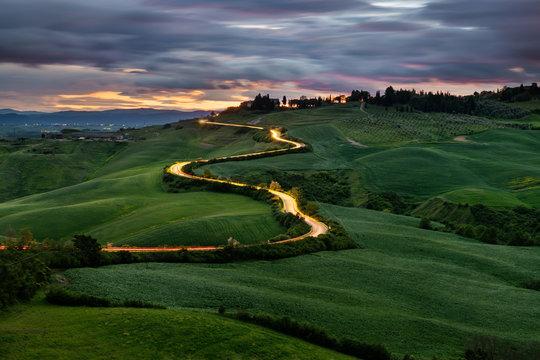 Kręta droga, światła samochodów, zachód słońca w tle, Toskania, Włochy