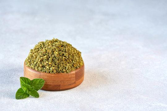 Mixed spice zaatar or zatar in wooden bowl on stone background