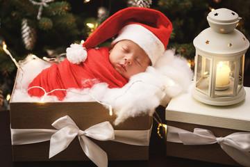Cute newborn baby wearing Santa Claus hat is sleeping in the Christmas gift box