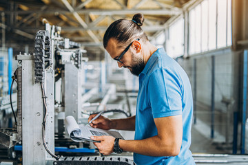 A worker in glasses standing near industrial equipment and verifies production data. Man holding folder in hands