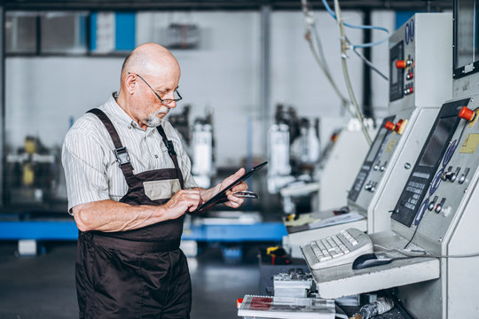 Adult proffesional worker on the factory working with machinery. A man stands with a tablet in his hands, checking the serviceability of the machines
