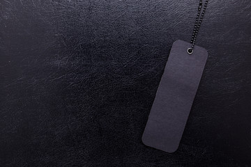 Black label on black isolated background close-up.