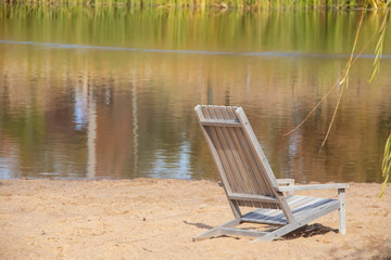 Dreamy scene of wooden beach chair in sand with reflections of reeds in water and willow branches on side - selective focus.