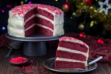 Piece of homemade red velvet cake with cream cheese frosting on a metal plate, low key photo with boke lights and christmas decoration on background,  horizontal