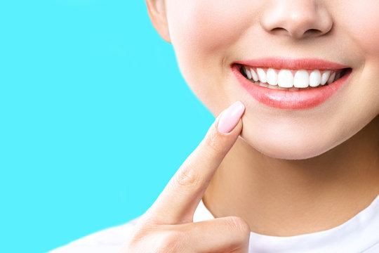 Perfect healthy teeth smile of a young woman. Teeth whitening. Dental clinic patient. Image symbolizes oral care dentistry, stomatology. blue Background