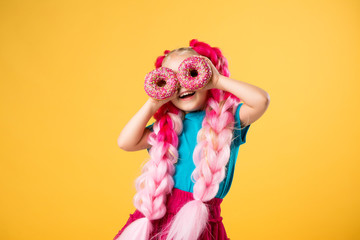 little girl with donuts on yellow background isolate, space for text