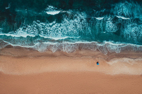 Aerial top view from drone of sandy beach with turquoise sea waves with copy space for text