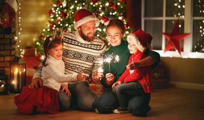 happy family mother, father and children celebrate Christmas and new year, light sparklers.