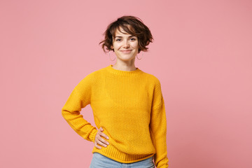 Smiling young brunette woman girl in yellow sweater posing isolated on pastel pink wall background, studio portrait. People sincere emotions lifestyle concept. Mock up copy space. Looking camera.