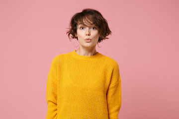Amazed pretty young brunette woman girl in yellow sweater posing isolated on pastel pink wall background studio portrait. People sincere emotions lifestyle concept. Mock up copy space. Looking camera.