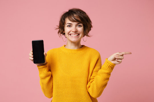 Smiling young woman girl in yellow sweater posing isolated on pastel pink background. People lifestyle concept. Mock up copy space. Hold mobile phone with blank empty screen, point index finger aside.