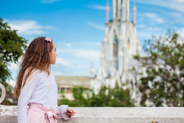 Beautiful young girl on the Ortiz Bridge looking at the famous gothic church of La Ermita built on 1602 in the city of Cali in Colombia