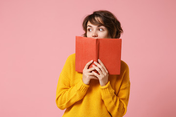 Young brunette woman girl in yellow sweater posing isolated on pink wall background studio portrait. People sincere emotions lifestyle concept. Mock up copy space. Holding covering mouth with book.