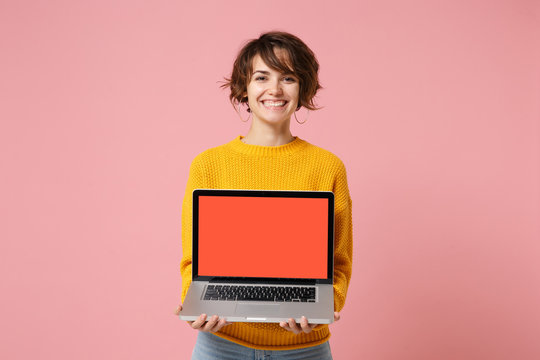 Smiling young brunette woman girl in yellow sweater posing isolated on pink wall background in studio. People lifestyle concept. Mock up copy space. Holding laptop pc computer with blank empty screen.