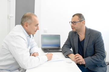 A man at the doctors appointment tells complaints. Bright medical room, professional medical consultation
