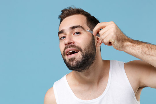 Close up bearded young man 20s years old in white shirt hold in hand tweezers isolated on blue pastel background, studio portrait. Skin care healthcare cosmetic procedures concept. Mock up copy space.