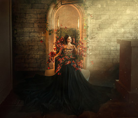 gothic dark queen sits in castle on golden throne. black dress with butterflies. Brick wall, large gothic room, magical sun rays from window. Long train fashionable silk skirt. Glamorous fantasy woman