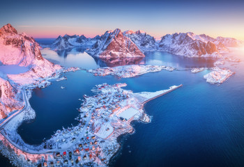 Obraz Aerial view of Reine at sunrise in winter. Top view of Lofoten islands, Norway. Landscape with blue sea, snowy mountains, high rocks, village with buildings, rorbu, blue sky, reflection in water - fototapety do salonu
