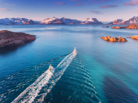 Aerial view of fishing boats, rocks in the blue sea, snowy mountains and colorful sky with clouds at sunset in winter in Lofoten islands, Norway, Landscape with two motorboats. Top view. Travel