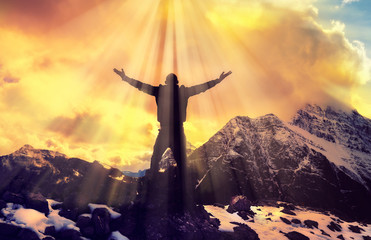 Inspirational Silhouette Of Man Worship Praise On Mountain Top With Light Rays And Glorious Clouds Religious Concept