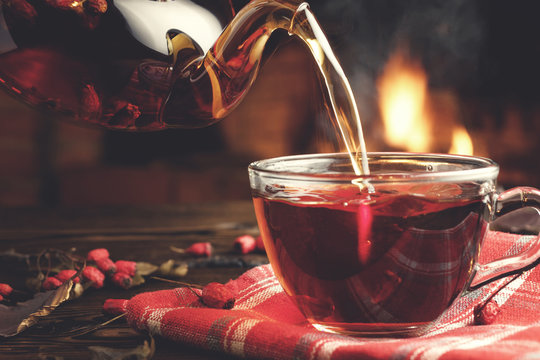Pouring hot tea with hawthorn into a glass cup in a room with a burning fireplace in the background