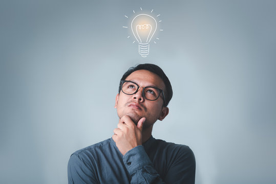 Thinking asian man in glasses looking up with light idea bulb above head on gray background.creative idea.Concept of idea and innovation
