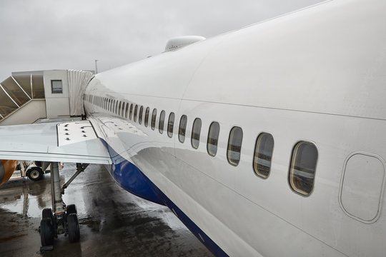 Passenger aircraft fuselage detail at an airport with jet bridge connected for boarding