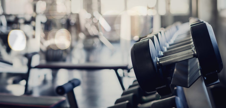 gym interior background of dumbbells on rack in fitness and workout room