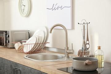 Set of clean dishware near kitchen sink