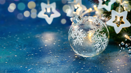 glass ball, green christmas tree branch and garland lights on blue background with confetti