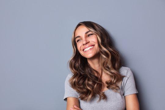 Beautiful smiling woman studio shot on gray background.