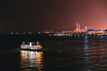 Fototapete - Ferry passing victoria harbour at night, Hong Kong