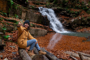 woman sitting on the log looking at waterfall autumn season