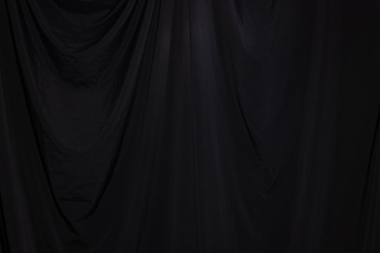 Black Curtain drape wave with studio lighting, Wallpaper Background Texture Detail of light and shadow, stage opening screen for performance and music
